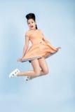 Junge Brunettefrau Smilling im orange Kleid, das auf blauen Hintergrund springt Stockfotografie