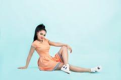 Junge Brunettefrau Smilling im orange Kleid, das auf Boden auf blauem Hintergrund sitzt Lizenzfreie Stockfotos