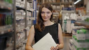 Junge Brunettefrau, -student, -auszubildender oder -angestellter, lächelnd beim das rechte Buch oder die Datei vom Büro herein wä stock footage