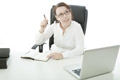 Junge Brunettegeschäftsfrau auf Schreibtisch hat eine Idee Stockfotografie