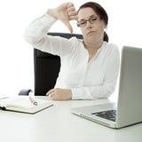 Junge Brunettegeschäftsfrau auf Schreibtischdaumen unten stockfotos