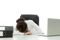 Junge Brunettegeschäftsfrau fallen schlafend auf Schreibtisch Lizenzfreie Stockbilder