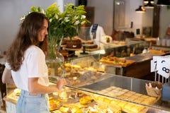 Junge Brunettelächelnfrau nahe moderner Anzeige der Bäckerei mit verschiedenen Arten des Plätzchens und Brötchen und wählen und m stockbild