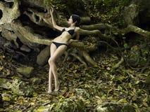 Junge Brunetteschönheit in einem tropischen Wald Stockbilder