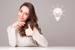 Junge Brunetteschönheit mit Glühlampesymbol Lizenzfreie Stockbilder