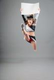 Junge Cheerleader On Gray Background Lizenzfreies Stockfoto