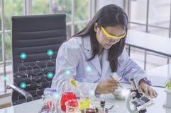 Junge Chemikerfrau, im Labor, Beispielschönheits-Produkte arbeitete mit den bunten flüssigen Chemikalien, die für Kosmetik in-vit Stockbild
