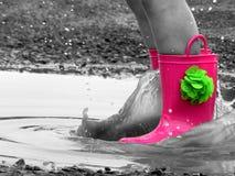 Junge Childs-Stiefel, die in einer Pfütze spritzen lizenzfreies stockfoto