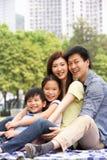 Junge chinesische Familie, die sich zusammen im Park entspannt Lizenzfreie Stockfotografie