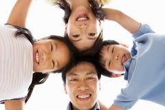 Junge chinesische Familie, die unten Kamera untersucht Stockbild
