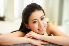 Junge chinesische Frau, die sich zu Hause auf Sofa entspannt Stockfoto