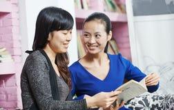 Junge chinesische Mädchen mit Buch in der Bibliothek Stockbilder