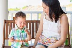 Junge chinesische Mutter, die mit ihrer Mischrasse chinesisch und dem kaukasischen Jungen genie?t seine Eist?te sitzt lizenzfreies stockbild