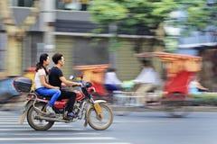 Junge chinesische Paare auf einem Motorrad Stockbild