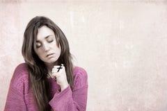 Junge christliche Frau, die ein Kreuz hält Lizenzfreie Stockfotos