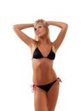 Junge dünne blonde Frau in der schwarzen Bikinistellung Stockfotografie