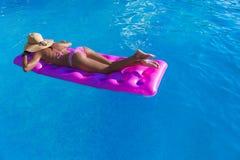 Junge dünne Brunettefrau im Strohhut erhält Sonnenbräune auf einer Luftmatte lizenzfreies stockbild