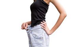 Junge dünne Frau in den Überformatpaaren Blue Jeans über Weiß lizenzfreie stockbilder