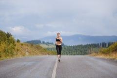 Junge dünne Frau in der Sportkleidung, die auf der Straße rüttelt Lizenzfreie Stockfotos