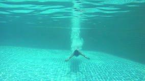 Junge dünne Frau des Brunette springt und schwimmend unter Wasser im Pool 1920x1080