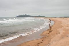 Junge dünne Frau, die auf einer verlassenen Küste steht Lizenzfreie Stockfotografie