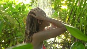 Junge dünne Frau, die eine Auffrischungsdusche in einem tropischen Garten genießt Langsame Bewegung