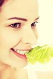 Junge dünne Frau, die Kopfsalat isst Lokalisiert auf Weiß Stockbild