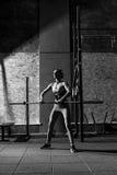 Junge dünne Frau, die mit einer langen Metallstange trainiert stockfotos