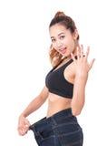 Junge dünne Frau, die zu große Jeans mit dem Zeigen des Fingers trägt Stockbilder