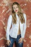 Junge dünne schöne junge blonde Frau mit den langen Beinen und dem Haar im Chaoshemd und -jeans Stockfotos