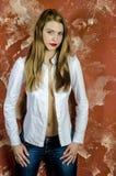 Junge dünne schöne junge blonde Frau mit den langen Beinen und dem Haar im Chaoshemd und -jeans Stockfoto