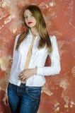 Junge dünne schöne junge blonde Frau mit den langen Beinen und dem Haar im Chaoshemd und -jeans Stockbild
