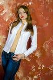 Junge dünne schöne junge blonde Frau mit den langen Beinen und dem Haar im Chaoshemd und -jeans Lizenzfreie Stockfotografie