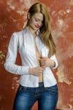 Junge dünne schöne junge blonde Frau mit den langen Beinen und dem Haar im Chaoshemd und -jeans Stockfotografie