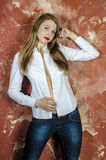 Junge dünne schöne junge blonde Frau mit den langen Beinen und dem Haar im Chaoshemd und -jeans Lizenzfreie Stockfotos