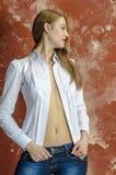 Junge dünne schöne junge blonde Frau mit den langen Beinen und dem Haar im Chaoshemd und -jeans Lizenzfreies Stockfoto