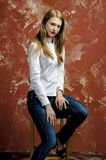 Junge dünne schöne junge blonde Frau mit den langen Beinen und dem Haar im Chaoshemd und -jeans Lizenzfreies Stockbild