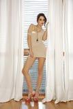 Junge dünne sexy Frau in der braunen Strickjacke gegen das Fenster Stockbilder