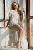 Junge dünne sexy Frau in der braunen Strickjacke gegen das Fenster Lizenzfreie Stockfotos