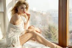 Junge dünne sexy Frau in der braunen Strickjacke gegen das Fenster Lizenzfreies Stockbild