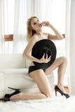 Junge dünne sexy schulterfreie Frau im schwarzen Hut gegen das Fenster Stockfotografie