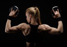 Junge dünne starke muskulöse Frau, die im Studio mit Dummkopf aufwirft Lizenzfreies Stockbild