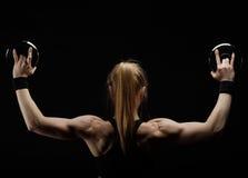 Junge dünne starke muskulöse Frau, die im Studio mit Dummkopf aufwirft Lizenzfreie Stockfotos