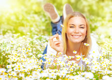 Junge Dame auf Gänseblümchenfeld Stockfoto
