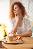Junge Dame der erstaunlichen Rothaarigen, die im Café beim Essen des Nachtischs sitzt Stockbilder