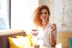 Junge Dame der erstaunlichen Rothaarigen, die im Café beim Essen des Nachtischs sitzt Stockfoto