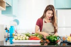 Junge Dame in der modernen hellen Küche Nahrung zubereiten stockfotos