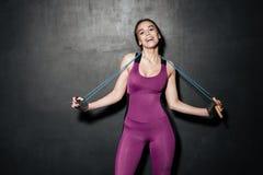 Junge Dame des glücklichen Sports, die Springseil halten steht Lizenzfreie Stockfotografie