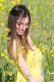 Junge Dame des netten Sitzes, die unter gelbem blühendem Feld steht Lizenzfreie Stockfotos