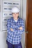 Junge Dame des Porträts tragender Hardhat durch elektrisches fusebox stockbilder
